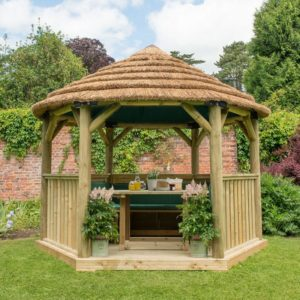 Forest Garden 3.6m Hexagonal Wooden Garden Gazebo with Thatched Roof - Furnished with Table, Benches and Cushions (Green)