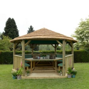 Forest Garden 4.7m Hexagonal Wooden Garden Gazebo with Thatched Roof - Furnished with Table, Benches and Cushions (Green)